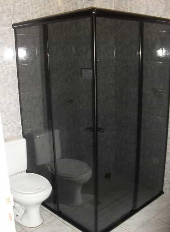 Box-para-Banheiro-Fumê-Canto. box para banheiro modelo 04 folhas de canto sendo 02 folhas fixas e 02 folhas móveis de correr. Box com perfil de acabamento em aluminio na tonalidade preta.