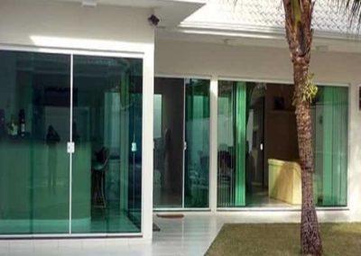 Janela de vidro verde temperado com perfil de acabamento em alumínio branco.