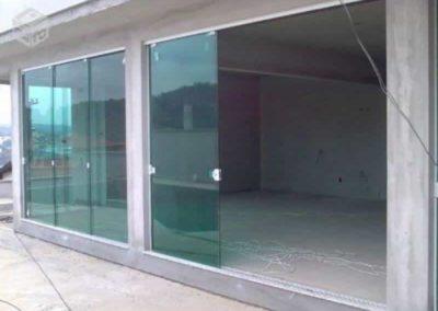 Porta de correr de vidro verde temperado de 8 mm, e acabamento em alumínio.
