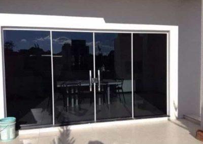 Porta de vidro fumê com vidro temperado de 8 mm, e acabamento em alumínio.